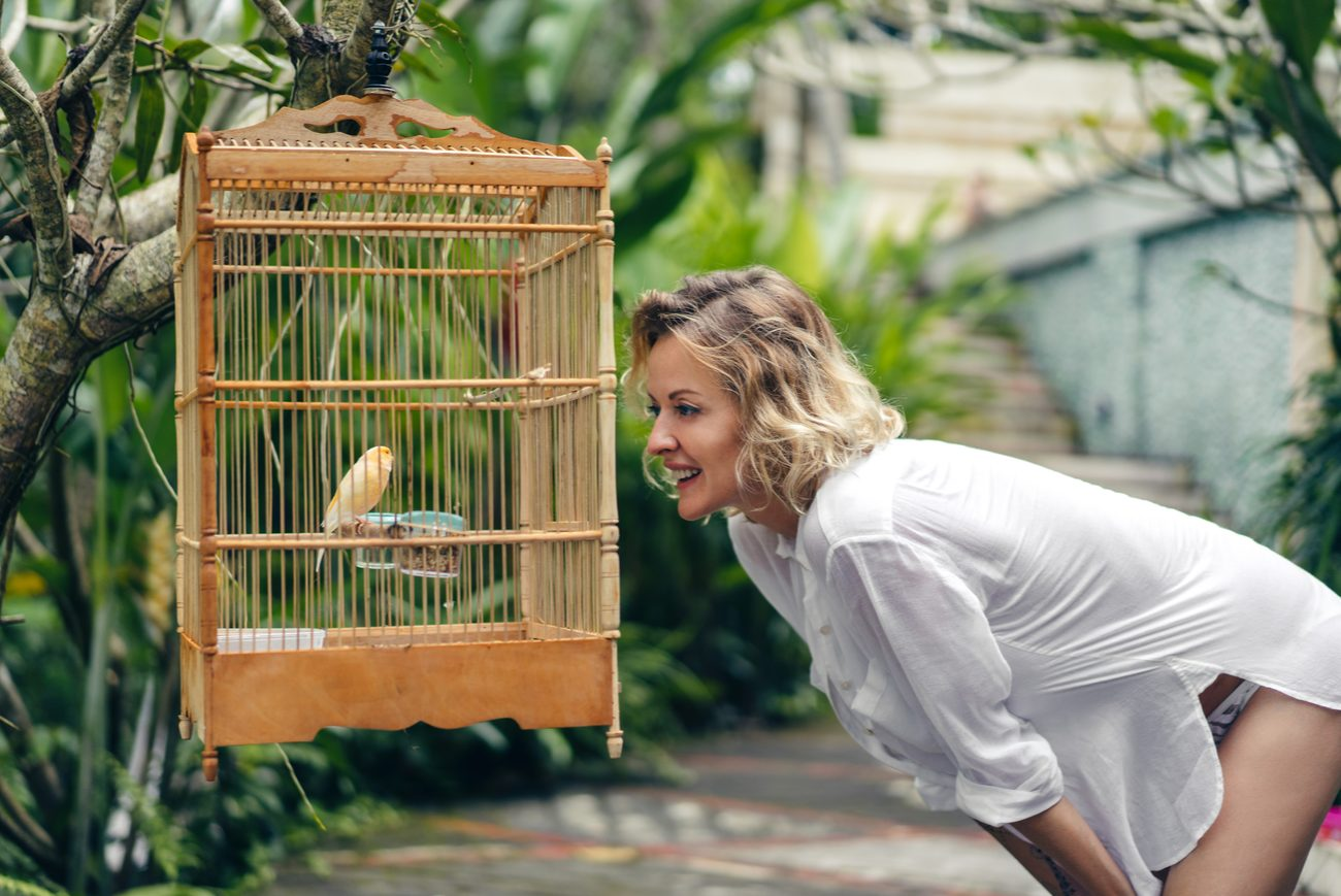 Young woman smiling at bird in a bird cage outside
